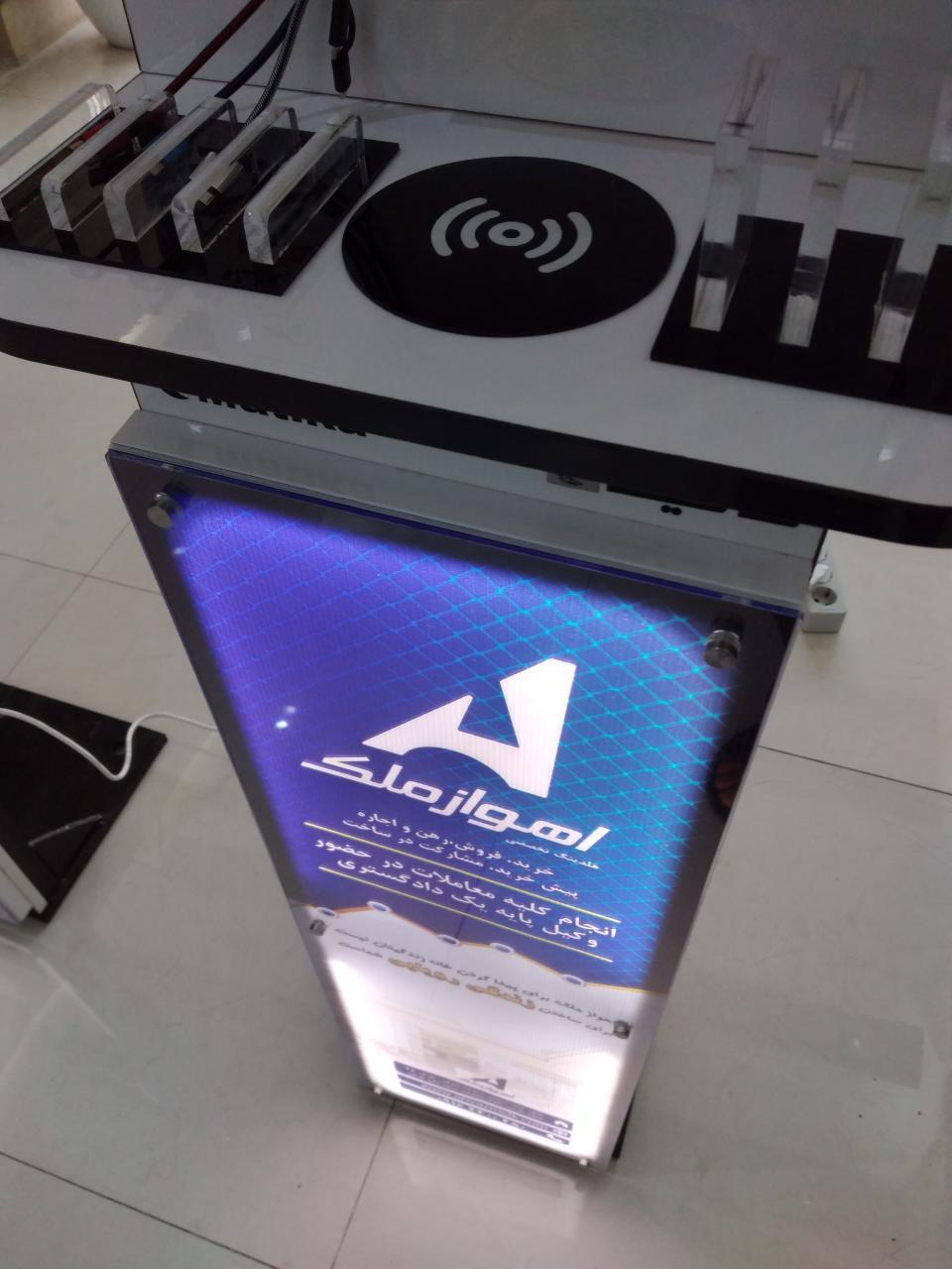 استند شارژر موبایل مدل TWIIP-LW پایه دار با ظاهری زیبا و کیفیت مناسب دارای قابلیت شارژ فست همزمان ۸ گوشی موبایل و تبلت از انواع مختلف و یک شارژر وایرلس روکار می باشد که باتوجه به ابعاد آن ۲۲×۱۳۲×۴۲ سانتی متر امکان قرار گیری و نصب روی زمین در هر نقطه ای را دارد و امکان نصب لوگو برند روی دستگاه وجود دارد و همچنین دارای فضای تبلیغاتیCM ۲۸×9۰ به صورت لایت باکس در روی پایه ها می باشد، موبایلها در دوحالت عمودی و افقی امکان قرارگیری روی دستگاه را دارند. دستگاه دارای محافظ ولتاژ و پریزهای برق اضافی در پشت دستگاه می باشد، دستگاه دارای اسکلت فلزی و وزنی حدود ۲۰ کیلوگرم برخوردار است و از ثبات بسیار زیادی بر روی پایه ها برخوردار است.